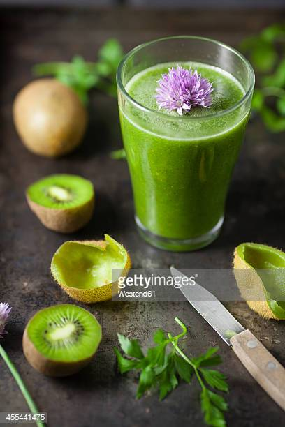 Glass of smoothie with kiwi, parsley and blooming chives, close up