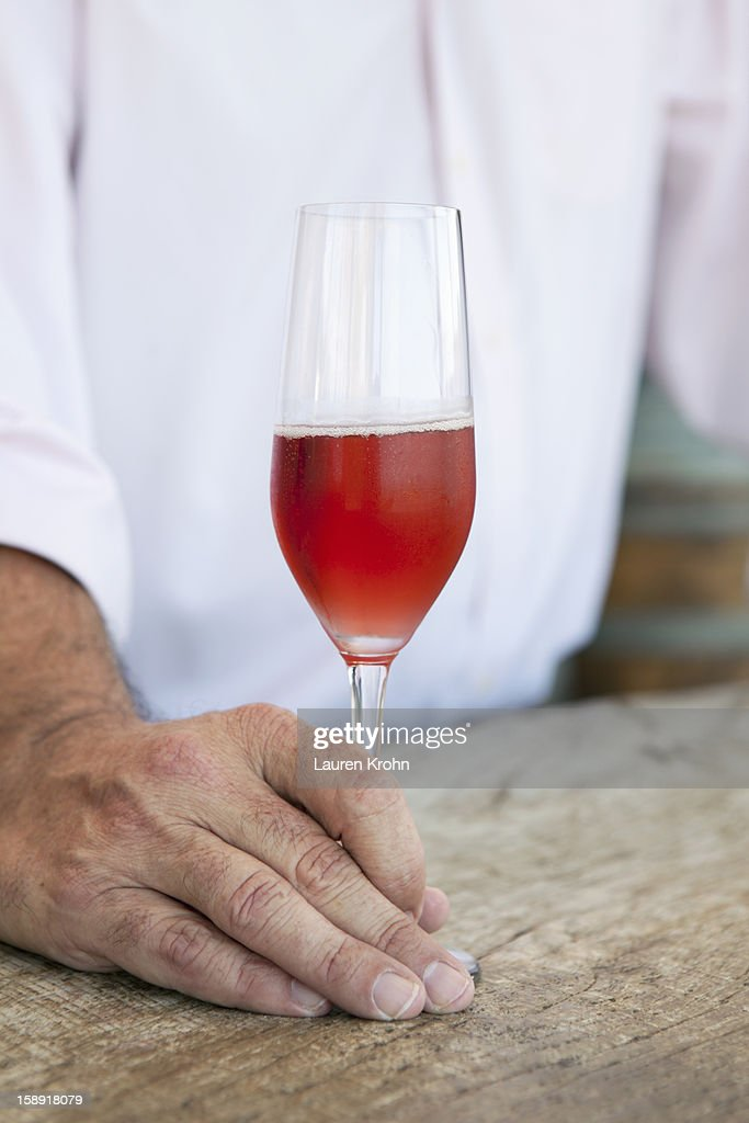 Glass of sparkling rose wine held on a bar top : Stock Photo