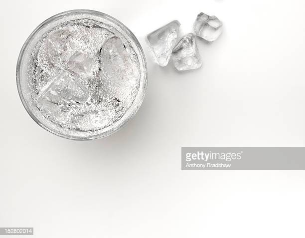 A glass of sparkling soda water with ice cubes
