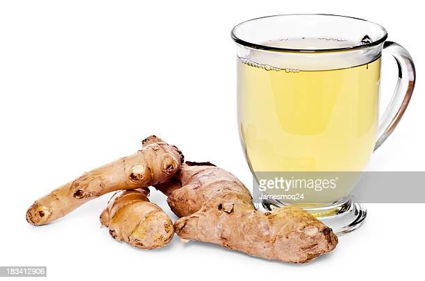 Glass of tea and ginger root on white background