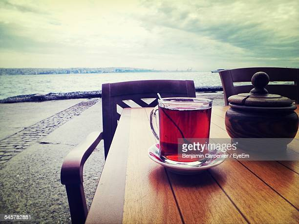 Glass Of Tea With Teapot On Table By Lake