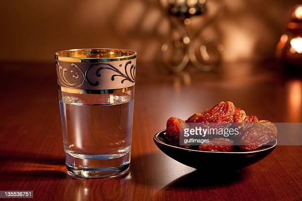 A glass of water and dates with illuminated lantern