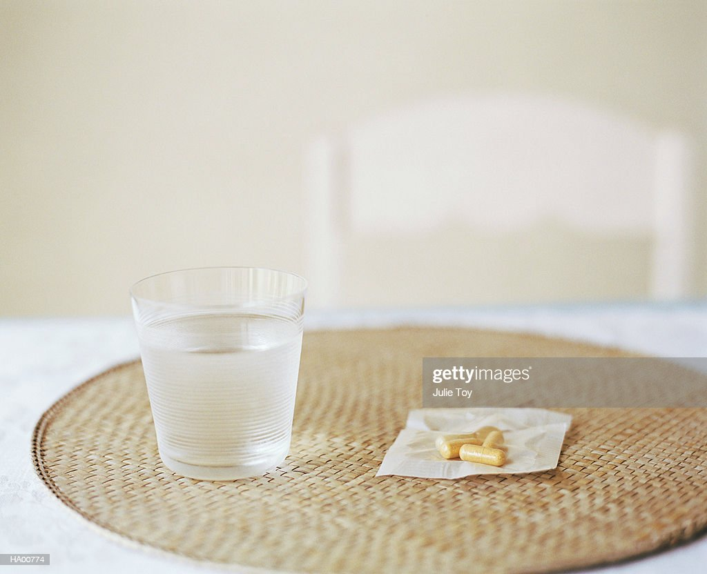 Glass of water and pills on placemat : Stock Photo