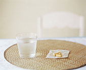 Glass of water and pills on placemat