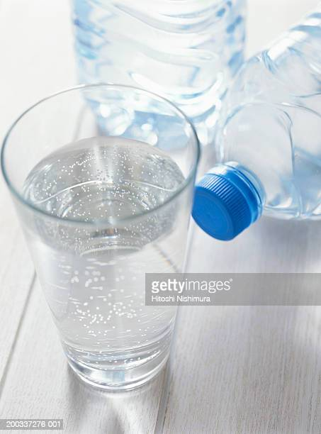 Glass of water and plastic water bottle, close-up, elevated view