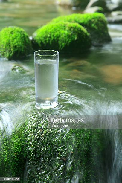 Glass of water near a mountain stream