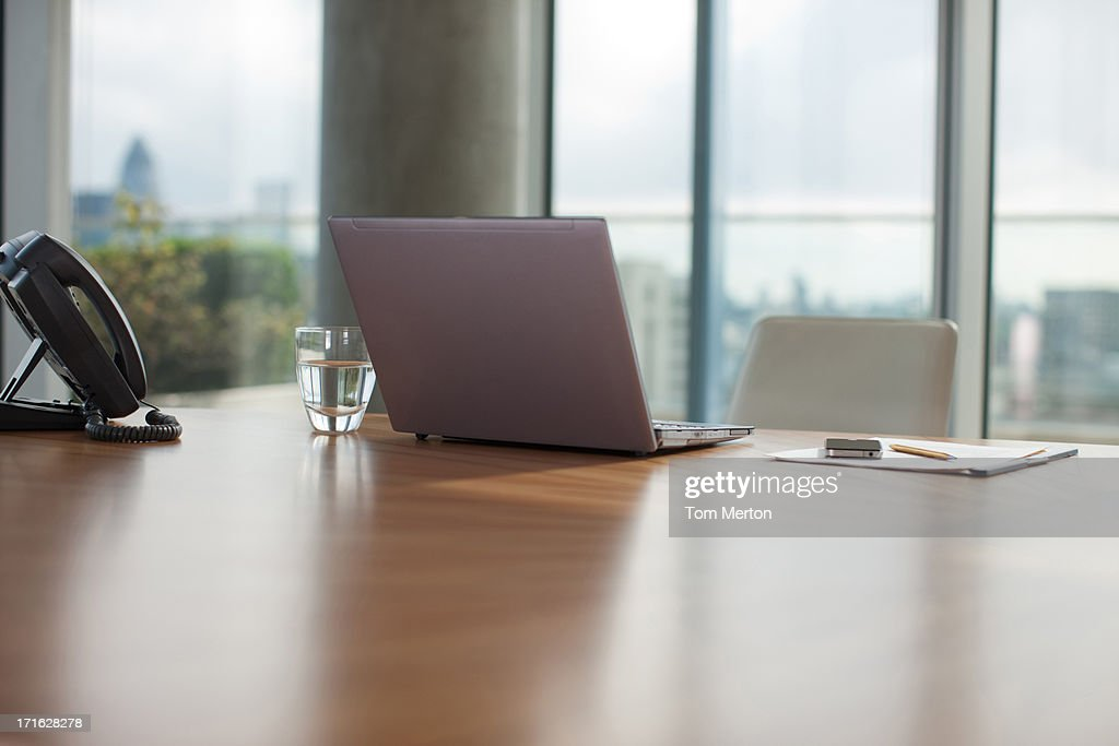 Glass of water, paper, laptop and pen on conference room table : Stock Photo