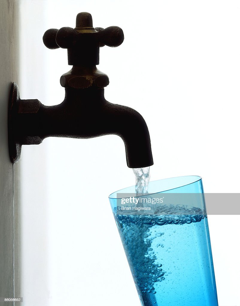Glass of water pouring from faucet : Stock Photo