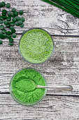 Glass of wheatgrass smoothie and bowl of wheatgrass powder