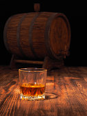 Glass of whiskey and vintage wooden barrel.
