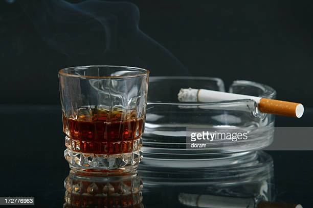Glass of whiskey next to a cigarette in an ash tray