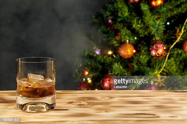 A glass of whiskey on a wooden table with a Christmas tree