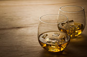 2 glasses of whiskey shot on a wooden table