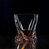 A glass of whiskey on a dark background