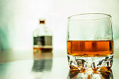 A glass of whiskey with a bottle in the background. Blurred Background