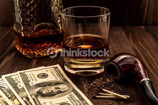 Glass Of Whiskey With A Money And Tobacco Pipe Stock Photo | Thinkstock