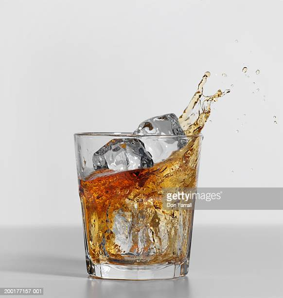 Glass of whiskey with ice cubes, liquor splashing out of glass