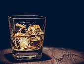 glass of whiskey with ice cubes on wood table, warm atmosphere, time of relax with whisky with space for text