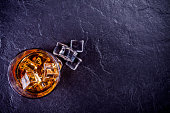 glass of whiskey with ice cubes on a stone background - top view