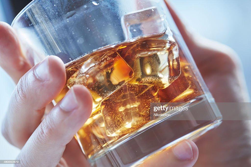 Vaso de whisky con hielo en su mano : Foto de stock
