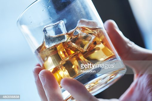 glass of whiskey with ice in his hand : Stock Photo
