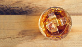 Glass of whiskey with ice on wooden background, Top view and blank text
