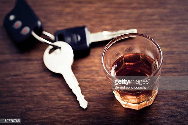 A glass of whisky and a set of car keys on a wooden table