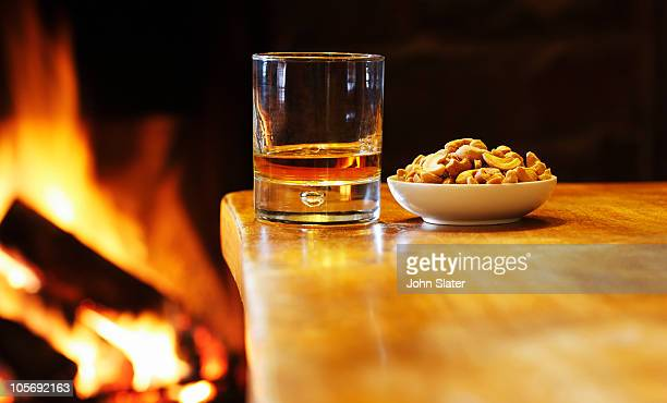 glass of whisky and cashew nuts at fireside