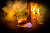 Glass of whisky on wooden bar closeup with bottles blurred view on dark background with light and smoke. Single glass of whisky on ice with a reflective wooden surface. Selective focus. Ready to serve