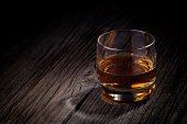 Glass of luxury single malt whiskey. Drink concept photography taken on old wooden table.