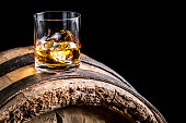 Glass of whisky with ice on old wooden barrel.