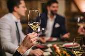 Close up of human hand holding a glass of white wine in restaurant