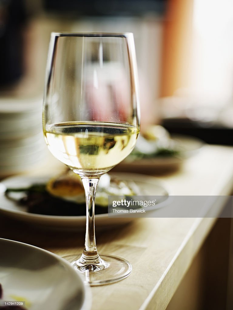 Glass of white wine sitting on countertop