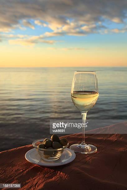 Copo de vinho e azeitonas no Mar