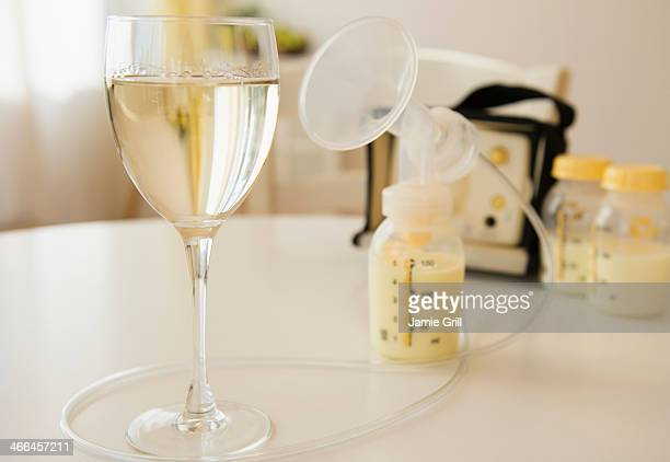 Glass of wine next to breast pump and breast milk