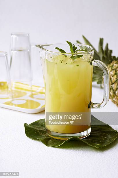 Glass pitcher of mint pineapple juice on pineapple leaf