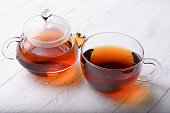 Glass teapot and cup with hot black tea on white wooden table