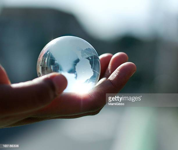 Glass toy of Earth in hand