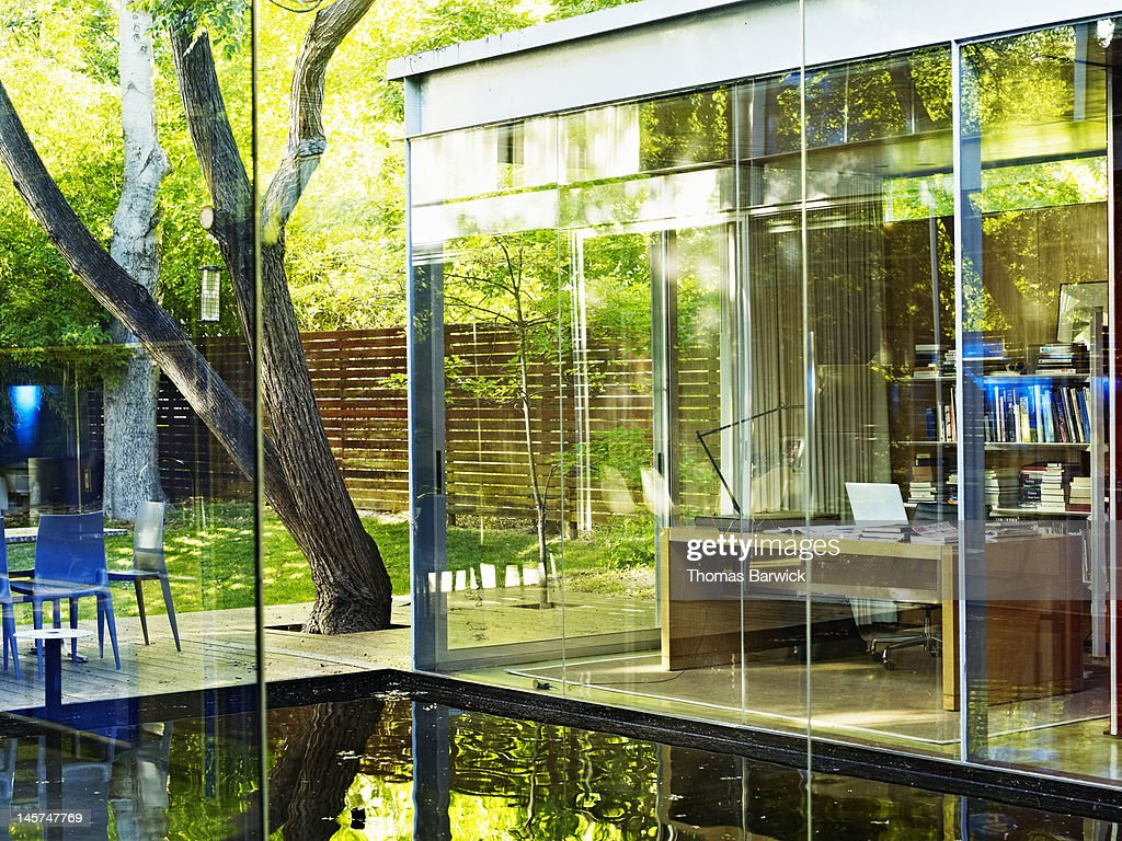 Glass walled home office in contemporary home : Stock Photo