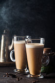 Two glasses with cold coffee latte macchiato on table against black background