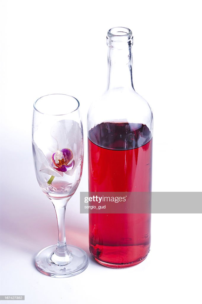 Vidro com vinho tinto e uma orquídea : Foto de stock
