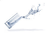 Glass with spilling water splash. Side view. On white background. Clipping path included.