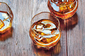 Glass with Whiskey on table rustic wooden background, top view