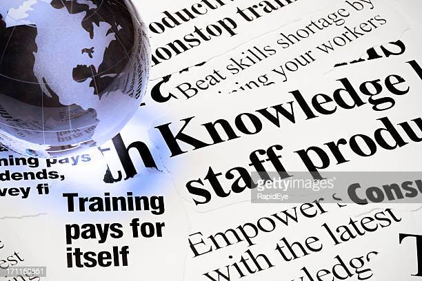 Glass world globe on newspaper headlines about staff training