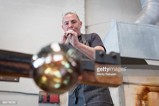 Glassblower blowing hot glass