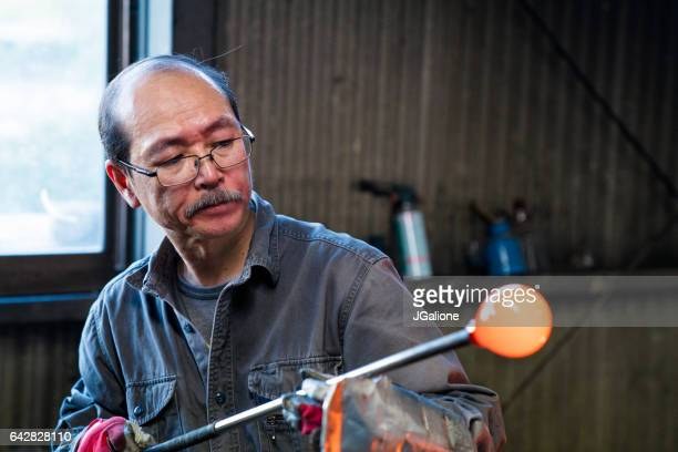 Glassblower inspecting his work