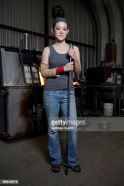 Glassblower is holding blowpipe, portrait.