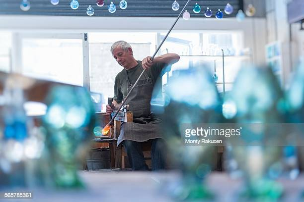 Glassblower with large blob of hot glass
