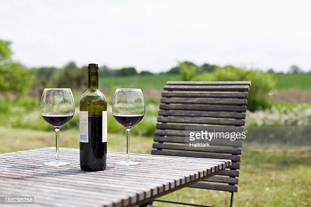 Glasses and a bottle of red wine on an outdoor setting