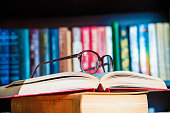 glasses and book on background bookcase close up